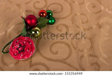Christmas cupcake with tree ornament on gold background - stock photo