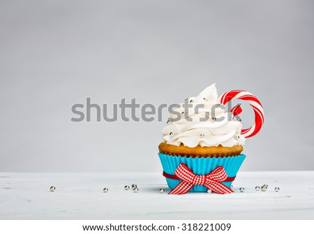 Christmas Cupcake with vanilla buttercream icing and a Candy Cane - stock photo