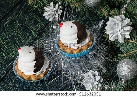Christmas cupcakes in the shape of funny penguins of meringue with chocolate on background decorated Christmas tree on a blue-green cracked background. Selective focus