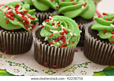Christmas cupcakes of red white and green, ready for a celebration.  Shallow depth of field. - stock photo