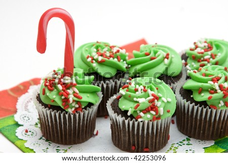 Christmas cupcakes topped with frosting, sprinkles and candy cane.