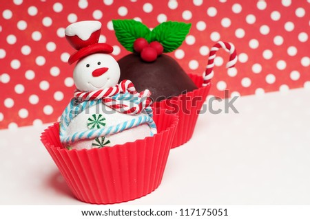 Christmas cupcakes with holly and snowman - stock photo