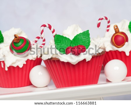 Christmas cupcakes with holly en candy canes - stock photo