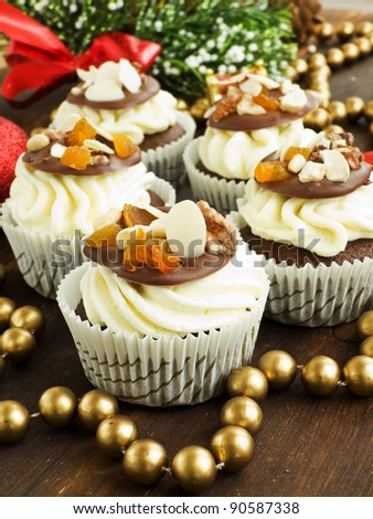 Christmas cupcakes with whipped cream and chocolate chip with nuts. Shallow dof. - stock photo