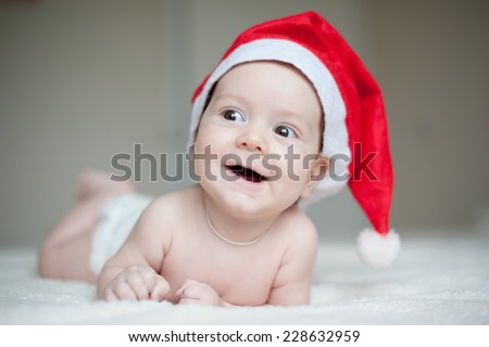 christmas cute baby boy/girl lying on red soft plaid like on snowdrift, beautiful funny infant in Santa's hat - stock photo