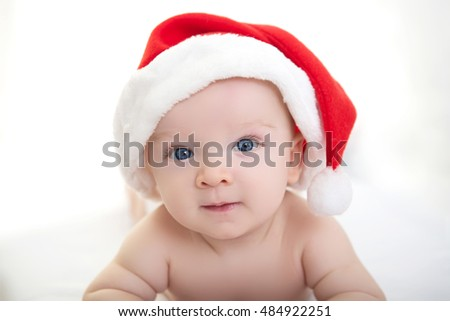 Christmas cute baby boy or girl lying on white like on snowdrift, beautiful funny infant in Santa's hat