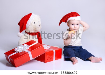 christmas cute baby boy sitting with gift boxes and toy bear, beautiful funny infant in Santa's hat eating rusk