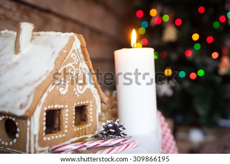 Christmas decor: gingerbread house, new year candle - stock photo