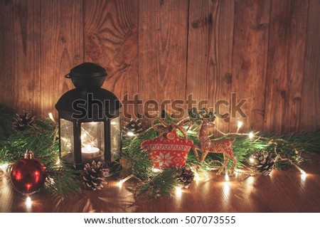 Christmas decor with candle garland lantern balls on wooden background