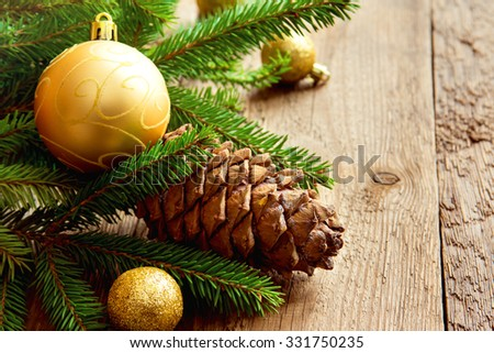 Christmas decor with cone, golden balls and branches of green fir on wooden background, copy space - stock photo