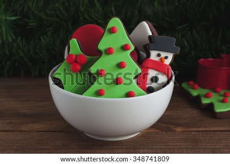 Christmas decorated cookies in small bowl on wooden background - stock photo