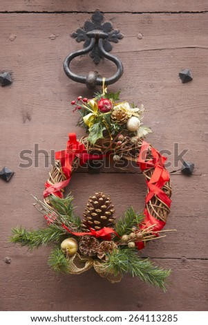 Christmas decorated wreath in an antique wooden door. France. Vertical - stock photo