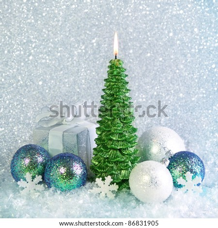 Christmas decoration and candle on blue background - stock photo