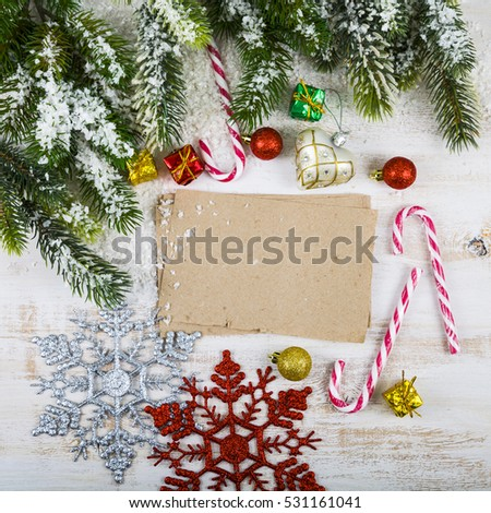 Christmas decoration and old paper on brown wooden table. Snowflakes, gifts, candies and fir branches on a wooden background.