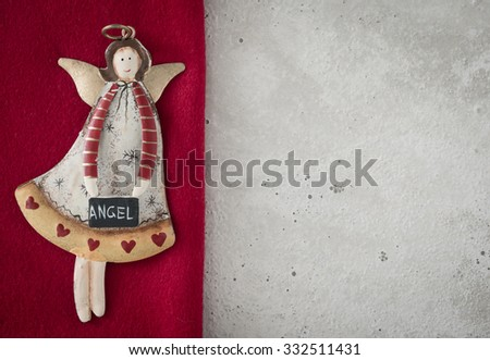 Christmas decoration, angel on red loden, concrete, copy space - stock photo