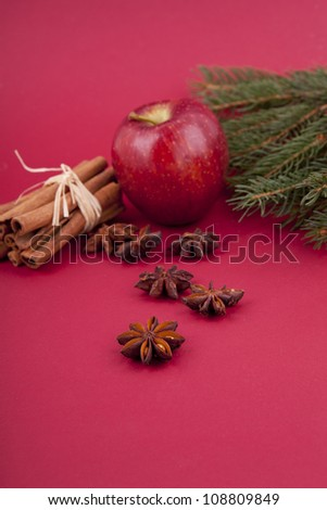 christmas decoration aromatic red apple, cinnamon, anise and tree on red background - stock photo