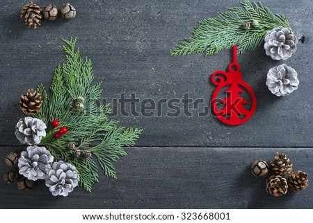 Christmas decoration background: red felt ornaments, pine and cypress cones with twigs on black wood table - stock photo