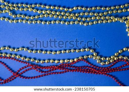 Christmas decoration beads on blue background - stock photo