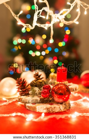 Christmas decoration. Candle, pine cones, bulbs, decorative band, lights... Shallow depth of field.