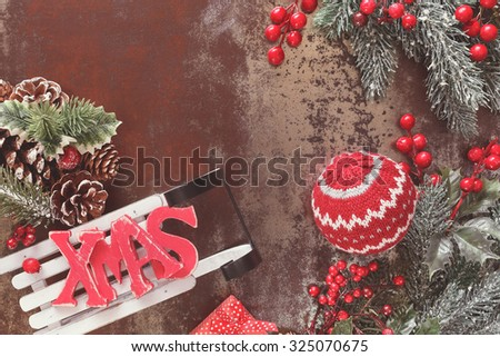 Christmas Decoration. Christmas background with woolly Christmas decoration and XMAS letters on sledge, rustic wood background with blank space, vintage style