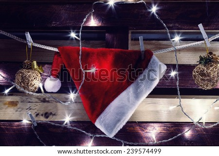 Christmas decoration - electric garland cap of Santa Claus and Christmas balls on a wooden background - stock photo