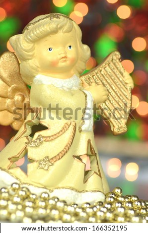christmas decoration, figure of angel playing the harp against bokeh background - stock photo