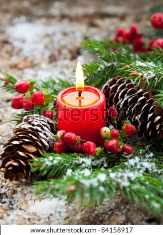 Christmas decoration: fir sprig,candle, cones and berries in snow - stock photo