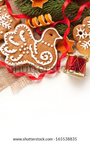 Christmas decoration. Gingerbread cookies with fir tree branches and dry orange on the white background. - stock photo