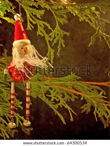 Christmas decoration hangs from a  branch illuminated  by the twinkling lights of the Christmas tree on a dark winter night with copy space. - stock photo