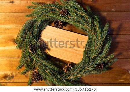 christmas, decoration, holidays and advertisement concept - close up of natural green fir branch wreath and wooden board - stock photo