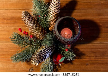 christmas, decoration, holidays and new year concept - close up of natural fir branch decoration and fir-cone and candle in lantern on wooden table - stock photo