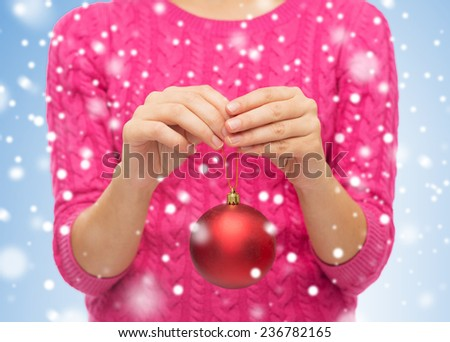 christmas, decoration, holidays and people concept - close up of woman in pink sweater holding red christmas ball over blue background with snow - stock photo