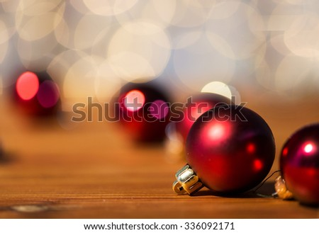 christmas, decoration, holidays concept - close up of red shiny balls on wood over golden lights background