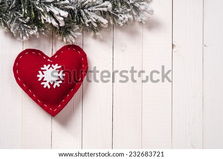 Christmas decoration in the form of heart with fir branches on wood background, with copy space - stock photo