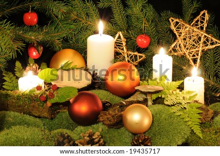Christmas decoration in the wood setting with Christmas balls, candles, moss, berries and mushrooms. - stock photo