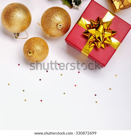 Christmas decoration isolated white. Red and golden gift boxes with three golden ball, and floral ornament. Top view. Square composition. - stock photo