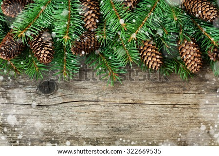 Christmas decoration of fir tree and conifer cone on texture wood background, magic snow effect, top view  - stock photo