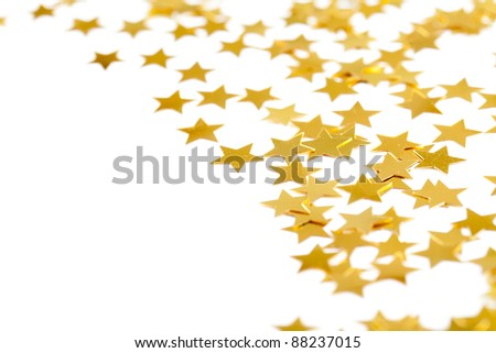 Christmas decoration of golden confetti stars against white background - stock photo