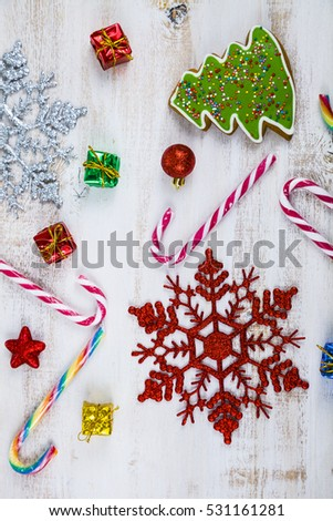 Christmas decoration on a wooden table. Snowflakes, gifts, candies and fir branches on a wooden background.