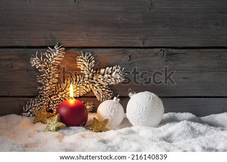 Christmas decoration on pile of snow against wooden wall - stock photo