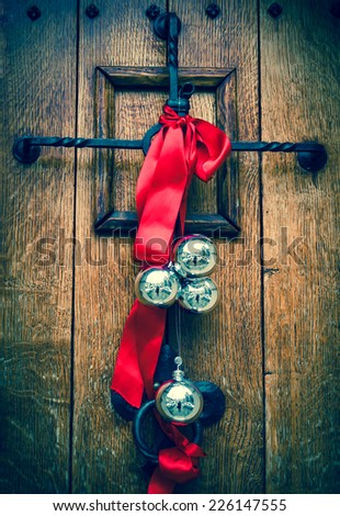 Christmas decoration on the wooden door. Red ribbon and four silver balls with street reflection. Aged photo. - stock photo