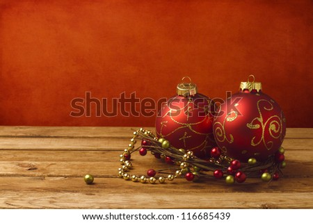 Christmas decoration on wooden table over red grunge background - stock photo