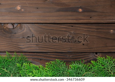 Christmas decoration: pine leaves on rustic brown wooden background