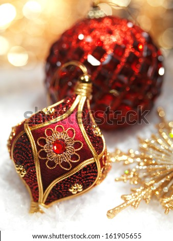 Christmas decoration red and gold ornaments on snow still life - stock photo