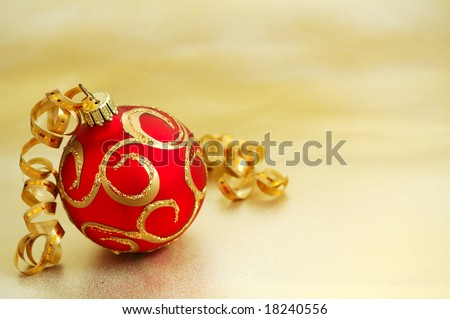 Christmas decoration. Red ball on golden background - stock photo