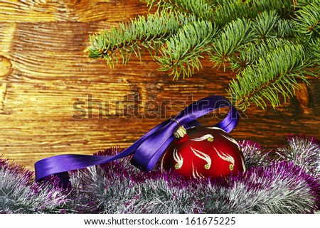 Christmas decoration. Red ball with violet ribbon, fir-tree and tinsel. Selective focus - stock photo