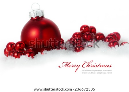 christmas decoration, red balls in snow isolated on white background, sample text in the copy space - stock photo