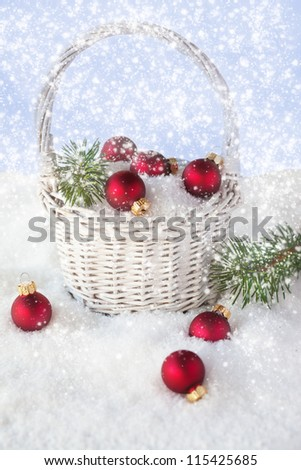 Christmas decoration - red balls in the basket with falling snow and branch of pine - stock photo