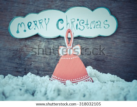 Christmas decoration red bell over grunge background with fake snow/ vintage handmade christmas decoration and letters Merry Christmas on wooden background - stock photo