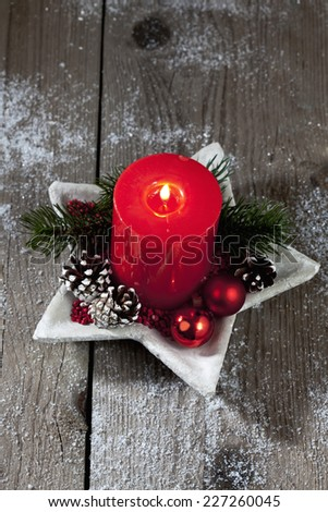 Christmas decoration, red candle, fir twig, Christmas sphere on wooden background - stock photo
